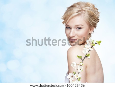 Gorgeous young blond smiling woman with spring flower branch on bright blue background