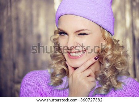Gorgeous young blond woman wearing a purple outfit flirting with the camera smiling and winking with a playful expression, with copy space - stock photo
