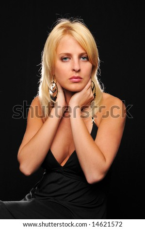 Gorgeous young blond woman wearing earrings against a black background