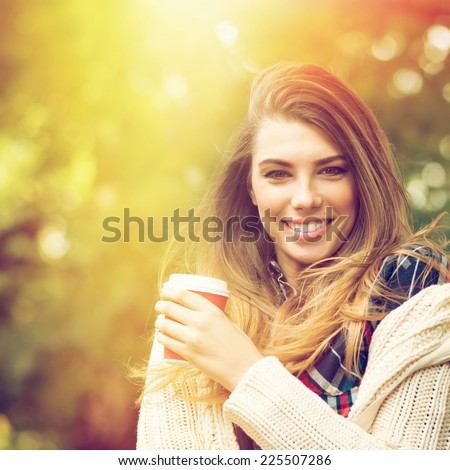 Gorgeous young blonde Caucasian woman with beautiful long hair and takeaway coffee in autumn in park smiling looking at camera. Square format image. - stock photo