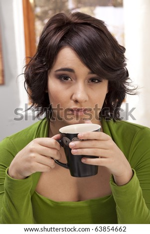 Gorgeous young brunette holding a mug of coffee with a tired expression. - stock photo
