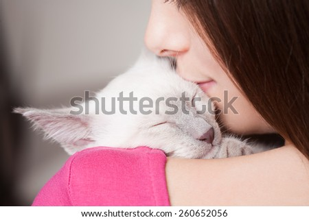 Gorgeous young brunette holding sweet young siamese kitten. - stock photo