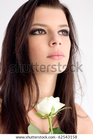 Gorgeous young brunette holding white rose.