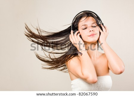 Gorgeous young brunette immersed in music wearing headphones.