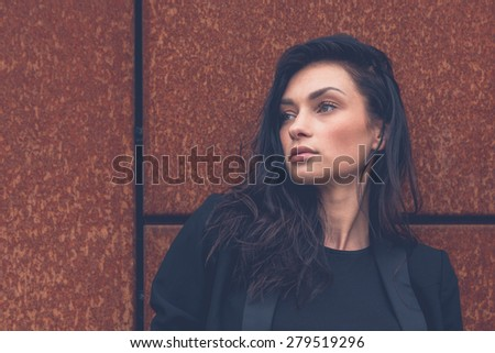Gorgeous young brunette in jeans posing on a rusty background - stock photo