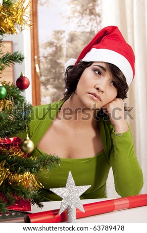 Gorgeous young brunette sitting next Christmas tree looking lonely. - stock photo