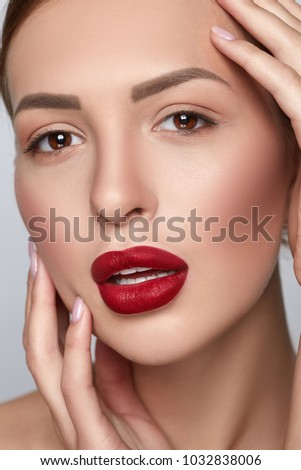 Gorgeous Young Brunette Woman face portrait. Beauty Model Girl with bright eyebrows, perfect make-up, red lips, touching her face. Sexy lady makeup. Grey background