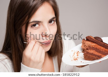 Gorgeous young brunette woman having creamy rich chocolate cake. - stock photo