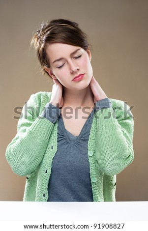 Gorgeous young brunette woman showing symptoms of neck pain. - stock photo