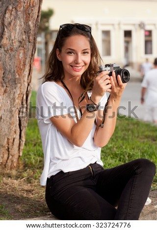 Gorgeous young brunette woman using analog camera. - stock photo
