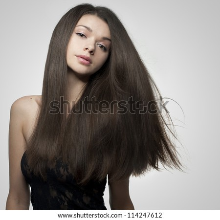 Gorgeous young brunette woman with  long, natural, healthy and shiny hair - stock photo