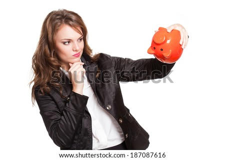 Gorgeous young brunette woman with orange piggy bank. - stock photo