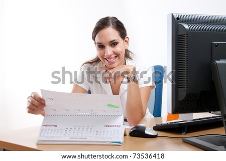 Gorgeous young businesswoman behind her desk. Checking her schedule. - stock photo
