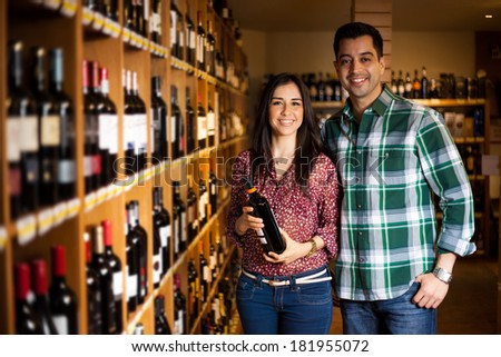 Gorgeous young couple buying a bottle of wine at the supermarket and smiling