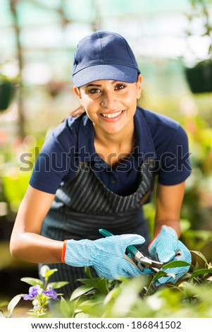 gorgeous young female florist working in nursery - stock photo