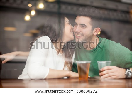 Gorgeous young flirty girl drinking beer with a guy in a bar and whispering in his ear - stock photo