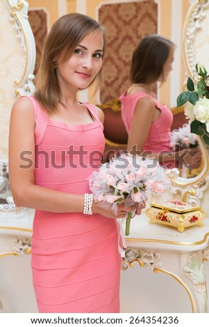 Gorgeous young girl standing and holding flowers, can be a bride - stock photo