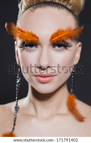 Gorgeous young model with perfect art make up and long false eyebrows made from feathers
