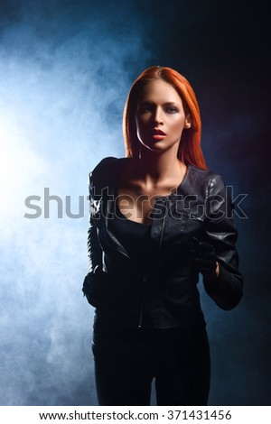 Gorgeous, young, redhead woman in black leather jacket being chased in the dusk. - stock photo