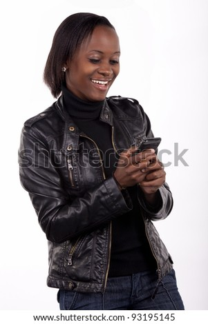 Gorgeous young South African woman reading a surprising message on her phone. - stock photo