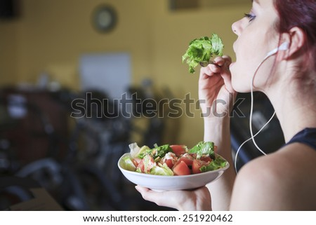 Gorgeous young woman at the gym eating salad - stock photo