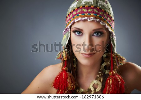 Gorgeous young woman, hat with tassels, golden jewelry, beautiful blue eyes, gray background.