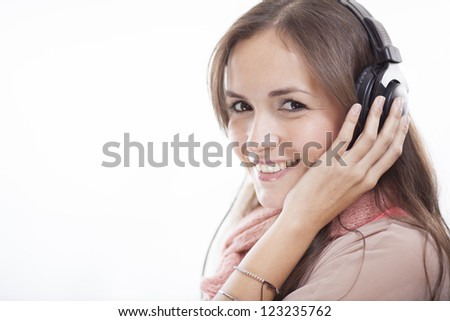 Gorgeous young woman listening to music and smiling - stock photo