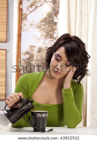 Gorgeous young woman pouring herself a cup of black coffee from a coffee-maker, with a tired expression. - stock photo