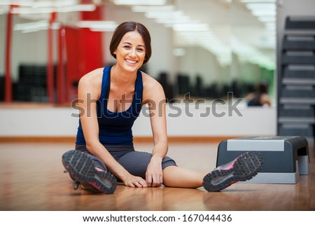 Gorgeous young woman sitting and taking a break from her workout at a gym - stock photo