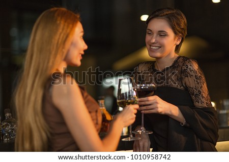 Gorgeous young woman smiling talking to her female friend over a glass of wine t the bar communication positivity lifestyle leisure celebrating elegance beauty party event youth carefree alcohol