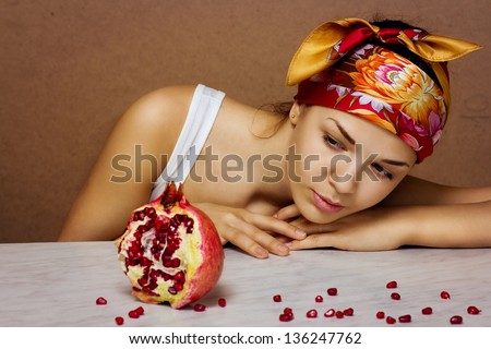 Gorgeous young woman wearing colorful scarf with Pomegranate - stock photo