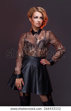 Gorgeous young woman wearing transparent blouse and leather skirt over dark background - stock photo
