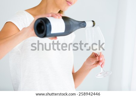 Gorgeous young woman with a glass of wine, pouring herself a glass of wine (shallow DOF; color toned image) - stock photo