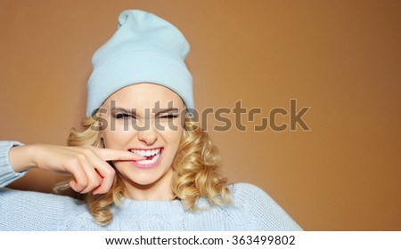 Gorgeous young woman with blond ringlets in a green knitted winter outfit and hat biting her finger - stock photo
