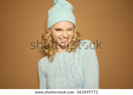 Gorgeous young woman with blond ringlets in a green knitted winter outfit blinking her eye - stock photo