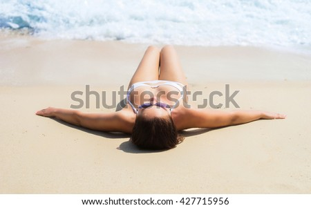 Gorgeous, young woman with perfect body  getting a tan on the beach.