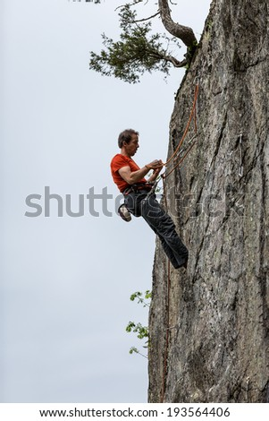 GORGES DU DAILLEY, SWITZERLAND - MAY 10: Rock climber prepares for descent in Gorges du Dailley on May 10, 2014 in Switzerland. Gorges du Dailley is one of many rock climbing spots in Switzerland.