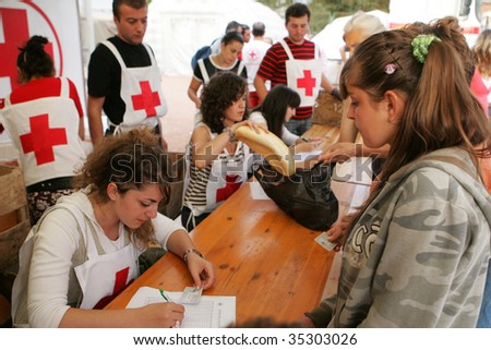 GORI, GEORGIA - SEPTEMBER 8: Red Cross workers distribute food at a refugee camp on September 8, 2008 in Gori, Georgia.