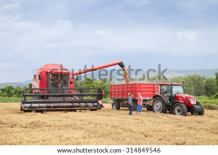 Gorna Oryahovitsa - July 3: Harvest of wheat. Harvester trailer filled with grain. Farmers harvest discuss the background of dramatic sky. On July 3, 2015, Gorna Oryahovitsa, Bulgaria - stock photo