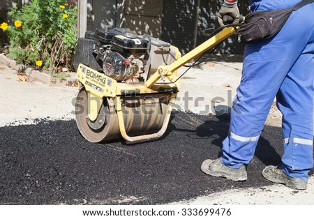 Gorna Oryahovitsa - October 6: Repair of city street, gasification and water. Rolling asphalt with handheld mini roller on October 6, 2015, Gorna Oryahovitsa, Bulgaria