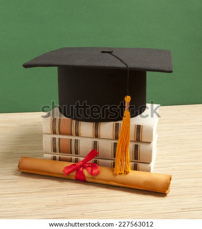 Gortarboard and graduation scroll, on a stack of old battered book - stock photo