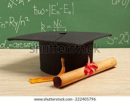 Gortarboard and graduation scroll, on the background of school board - stock photo