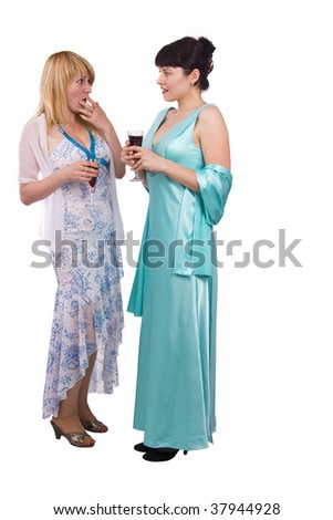 Gossip - two beautiful girls in studio shot.  Girl in greenness of the sea dress is standing and holding wine glass. Woman in white dress is telling a secret to another. Isolated on white background.