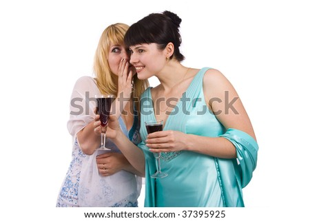 Gossip - two beautiful girls in studio shot.  Happy young women friends talking and laughing.  Girl in greenness of the sea dress is standing and holding wine glass. - stock photo