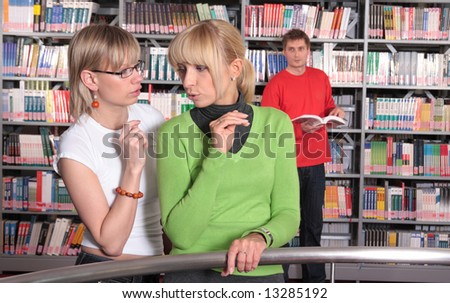 Gossip.Two women chatting, standing by a railing, inside a library, man in background looking at them - stock photo