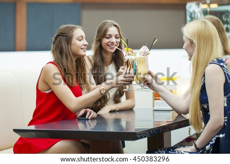Gossiping by the cocktail. Close up four attractive young women drinking cocktails in shopping mall and having a talk with their friend - stock photo