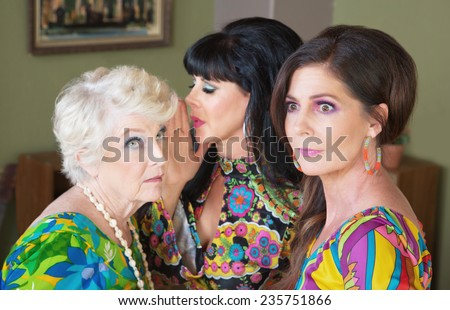 Gossiping ladies sharing secrets and whispering to each other - stock photo