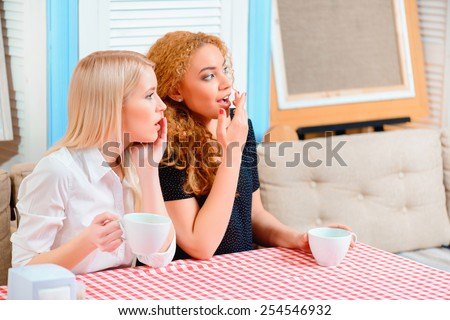 Gossiping. Two beautiful young women gossiping and drinking coffee while sitting in the cafe  - stock photo