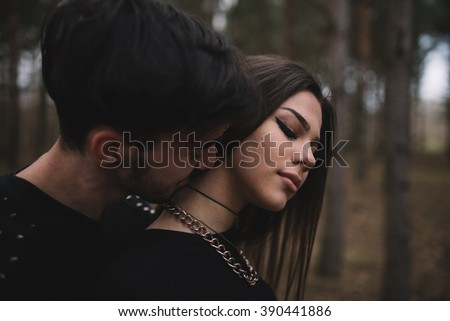 Goth boy kisses her girlfriend on the neck - stock photo