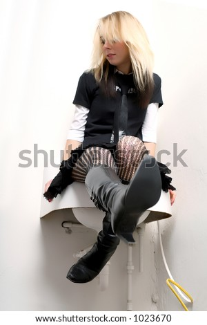 Goth girl on sink kicking out leather boot